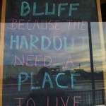 God created Bluff because the hardout need a place to live. Chalkboard message in shop window.